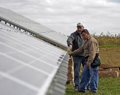 Jim Mitchell, left, of Woodside Farm Creamery in Hockessin, Del., looks over a solar panel installation with Marin Hernandez of Sun Technics. The dairy farm needs a lot of expensive refrigeration and solar power should provide up to 85% of the farm's power.
