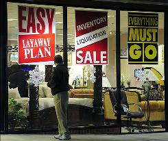 A man passes a furniture store advertising liquidation prices in Manassas, Va., in December.