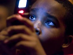 Jaz Young, 9, videotapes the inauguration of President Barack Obama on his cellphone Tuesday.