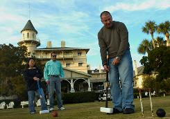 John Boatright takes a swing during croquet while Joy Brasher and Pablo Gallego watch at the Jekyll Island Club Hotel on Jekyll Island, Ga. The resort could be an alternative to higher-priced golf resorts.