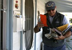Dennis Stecz delivers mail Wednesday in San Lorenzo, Calif. The Postal Service is considering five-day mail delivery.