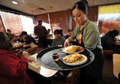 Liz Orozco serves breakfast to a table of customers at the Denny's on Burbank Boulevard in North Hollywood.