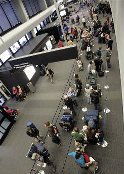 Passengers wait in long lines at the United Airlines domestic terminal at San Francisco International Airport in November. Fewer people are flying these days, and airfares have fallen.
