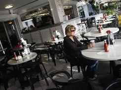 Shannon LeDuc drinks coffee at a mostly empty restaurant on the Ocean Drive strip in Miami Beach.