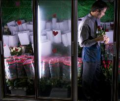 Stephen Caruso, of the fourth generation-owned Caruso Florist, checks a refrigerated case of roses Wednesday at Caruso's in Washington, D.C.