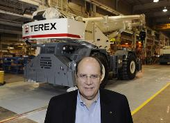 "Ron DeFeo, the CEO of Terex stands next to an assembly line at a Terex plant in Waverly, Iowa. ""If you combine technology with the hardware of an economy, the ports, waterways, roads, energy infrastructure, you are going to end up with a stronger economy,"" he says."