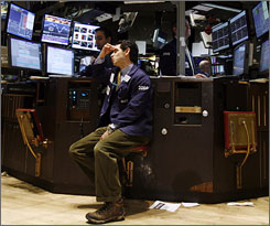 Traders react to the steep drop of the Dow on the floor of the New York Stock Exchange early Monday.