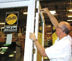 Gary Subbert, a Pella employee, tests hinges on a patio door in Carroll, Iowa. Some workers face four-day workweeks and one-week furloughs.