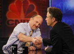 "Jim Cramer, left, of CNBC's ""Mad Money,"" shakes hands Thursday with Jon Stewart during Comedy Central's ""The Daily Show with Jon Stewart."""