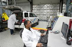 Lab techs William Davis, right, and Diego Hinojosa at Southern California Edison's Electric Vehicle Technical Center, in Pomona, Calif., conduct tests on a Ford Escape.