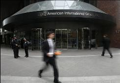 A man passes by an American International Group office building Monday in New York City. AIG used billions in federal aid to pay foreign banks, highlighting the expanse of the global financial system.