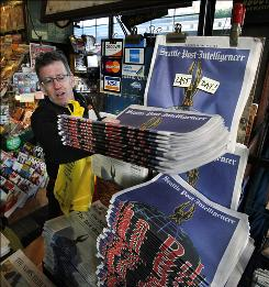 Wilber Hathaway stacks final editions Tuesday of the Seattle Post-Intelligencer in downtown Seattle.