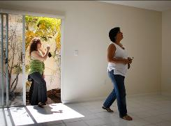 Eloisa De Oliveira, left, and her mother, Maria Zucearo, look at a home in Miami.