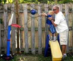 "Cliff Petty helps youngest son Landon, 2, shoot a basket in their backyard in Sunrise, Fla. Petty and his wife, Kara, are trying to cut back on child care costs without sacrificing the quality of care. ""My children's upbringing is more important than money,"" Petty says."