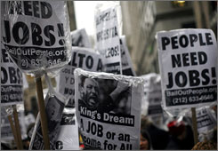 Protesters carry signs bearing the likeness of Dr. Martin Luther King, Jr. during a rally on Broadway near Wall Street Friday, April 3, 2009 in New York.