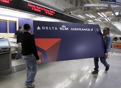 Shannon King, left, and Brian Vosberg carry a new Delta sign to the Northwest ticket counter at Minneapolis-St. Paul International Airport on March 30, 2009 .