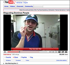 An image from the video on YouTube shows a Domino's employee sticking cheese pieces up his nose.