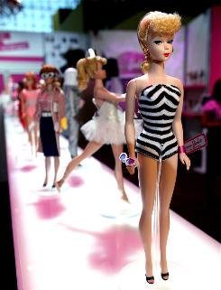 The 50th anniversary of Barbie is commemorated by a lineup of Barbie dolls from different eras.
