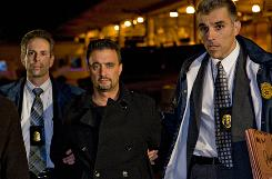 Nicholas Cosmo, center, accused of running a $370 million Ponzi scheme, is escorted in January by a U.S. Postal Inspection Service officer, right, and an FBI agent in New York.
