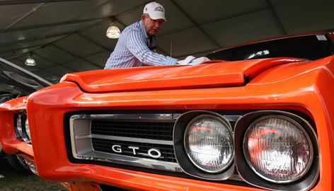 A 1969 Pontiac GTO gets a touch-up at the Barrett-Jackson auction in Scottsdale, Ariz., last year. GM is giving the ax to its 83-year-old Pontiac brand.