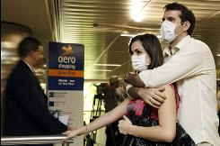 A mask-wearing couple at Sao Paulo's airport wait Monday for relatives arriving from Mexico. The U.S. advises Americans to avoid travel to Mexico.