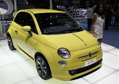 A woman poses next to a Fiat 500 displayed at the 79th Geneva Car Show in March 2009.