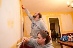 Kelly and Jim Butler paint a room in their new home in Stratford, Conn. They paid $213,000 for the foreclosed home, $76,000 less than the previous owners.