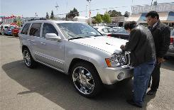 Anthony Marquez, left, buys a Jeep Grand Cherokee at a Chrysler dealership in Oakland on Thursday.