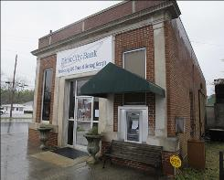 """The banner above The closed First City bank in Gibson, Ga., still reads """"Celebrating 100 Years of Service."""""""