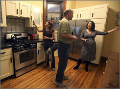 Linda, left, and Mark Fussell speak to Corcoran Group Real Estate salesperson Elisa Bond during an open house in Brooklyn as more buyers and bigger crowds are showing up at home showings.