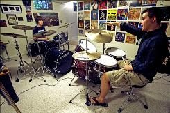 Eric Cieslewicz, 18, right, gives drum lessons to David Maue in the basement of Cieslewicz's home on May 13 in Milford, Ohio. He has eight students.