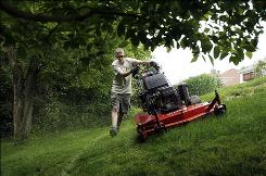 Lucas Rice cuts a client's lawn in Loveland, Ohio, before storms roll in on May 13.