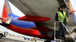 Steve Surla prepares to fuel up a Southwest jet last May in Oakland. Southwest, American and other carriers are venturing back into the oil hedging markets to reduce risk in the event of a price jump.