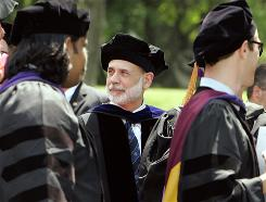 Federal Reserve Chairman Ben Bernanke watches as Boston college law school graduates proceed into their commencement ceremony.
