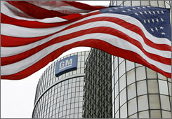 A flag flies in front of the General Motors headquarters in Detroit on Monday. GM filed for Chapter 11 bankruptcy protection as it moved to shrink its global operations.