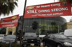 A GM dealership in Santa Monica, Calif. displays a sign indicating it is still in business despite the company's plans to close dealerships around the country following its bankruptcy.