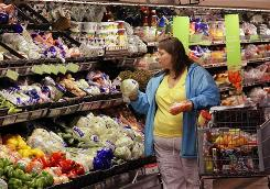 A shopper picks out groceries at a Wal-Mart Super Center in Springfield, Ill. The world's largest retailer credits its profits and sales growth to necessities and consumables such as food.