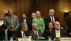 During a Senate Commerce Committee hearing on Chrysler and General Motors decision to slash dealerships, franchise owners in the audience stand while Chrysler President James Press, lower left, and GM President Fritz Henderson, right, sit at the witness table on Capitol Hill.