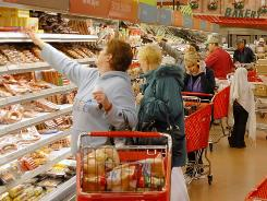 Shoppers stock up on groceries at a Super Target in Littleton, Colo. Since the recession consumers are choosing to spend more on non-discretionary items such as food and healthcare items and less on apparel and home products.
