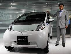 Mitsubishi President Osamu Masuko poses with the company's newly unveiled electric car, the i-MiEV, in Tokyo.