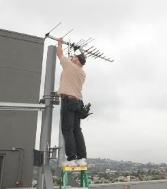 Ted Lewis of Ted's Master Antenna Service in Los Angeles installs a new antenna.