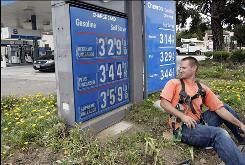 An electrician working on an in-ground power line takes a peek at the high gas prices at a Chevron dealership in South San Francisco on June 9, 2009.