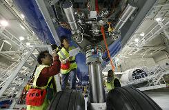Boeing workers check the front landing gear on a 787 at the plant in Everett, Wash., on April 30, 2009. Getting it into production has proved a bigger challenge than Boeing expected.