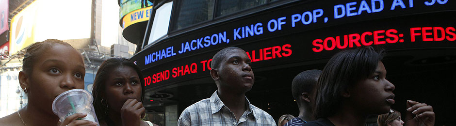 Onlookers are mesmerized by reports of the death of music icon Michael Jackson on large screens in Times Square in New York City on Thursday.