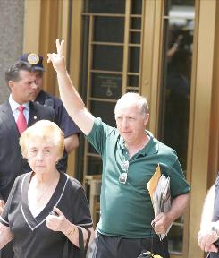 Michael DeVita, a victim of the Madoff's Ponzi scheme, holds up his hand in a victory symbol as he leaves the federal courthouse after Madoff received a sentencing of 150 years in prison.