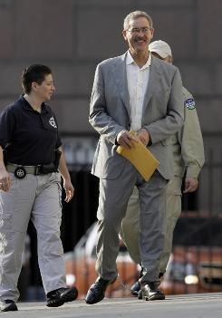 Texas billionaire Allen Stanford is escorted into federal courthouse in Houston on Monday.