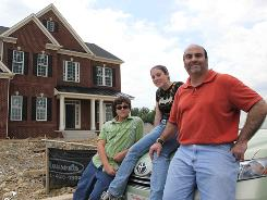 Victor Montalvo-Lugo, right, with children Isaac Montalvo and Amanda Fischer at their future home, which is under construction in Urbana, Md., on July 3. They have yet to sell their California home.