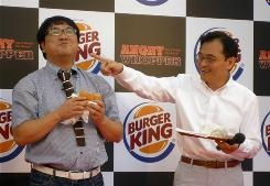 Burger King Japan President Hitoshi Arimoto, right, reacts as Japanese comedian Cunning Takeyama eats the Angry Whopper burger at a promotional event in Tokyo. The Angry Whopper, a spicy burger with jalapenos and hot sauce, is being introduced in Japan's sizzling fast-food market.