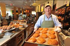 Panera CEO Ron Shaich in apron and hat, with a tray of asiago cheese bagels at a Panera Bread cafe in Needham.