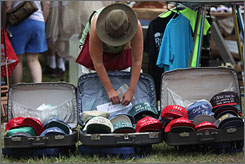 "Fawn Sensenig of Pottersdale, Pa., works on her hat display in Karthaus, Pa., during the ""100-mile yard sale"" through north-central Pennsylvania in July."